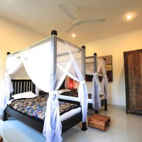 Bedroom with two large single beds with mosquito nets.