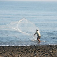 Man with fishing net on beach in Bali.