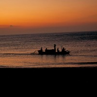 A fishing boat on the Bali sea at the setting of the sun.