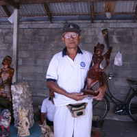 Men make traditional wooden statues in Bali.